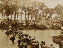 Photograph from Stordy - From Nairobi to the Red Sea, showing porters fording the Guaso Nyero