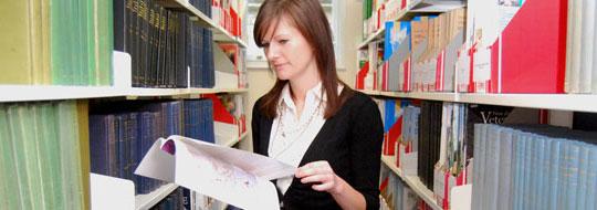 Woman amongst library bookshelves
